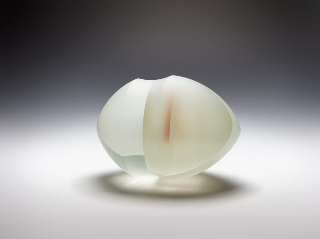 Large white carved translucent glass structure with a little bit of red inside, displayed on a white background