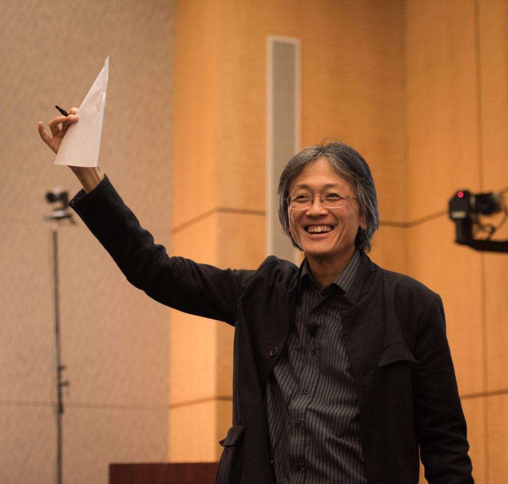 Man holding up a folded piece of paper during a presentation