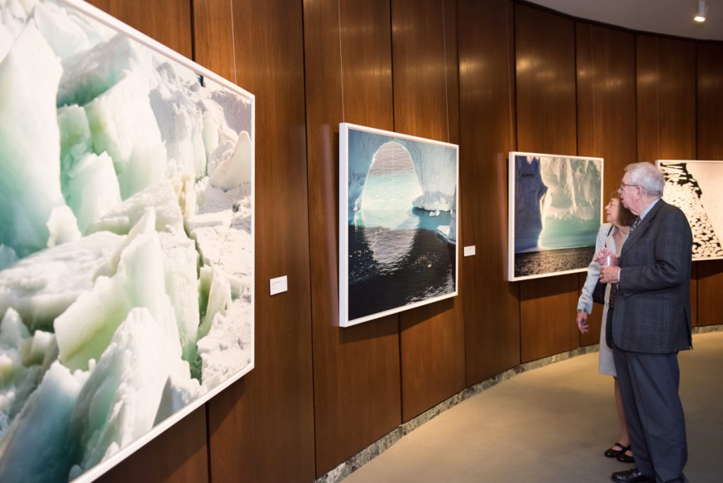 A man and woman looking at large photos of the arctic hanging on the wall