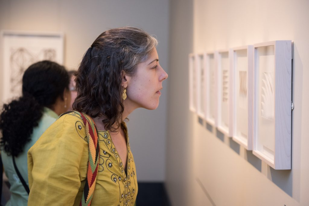 Woman closely looking at art hanging on the wall