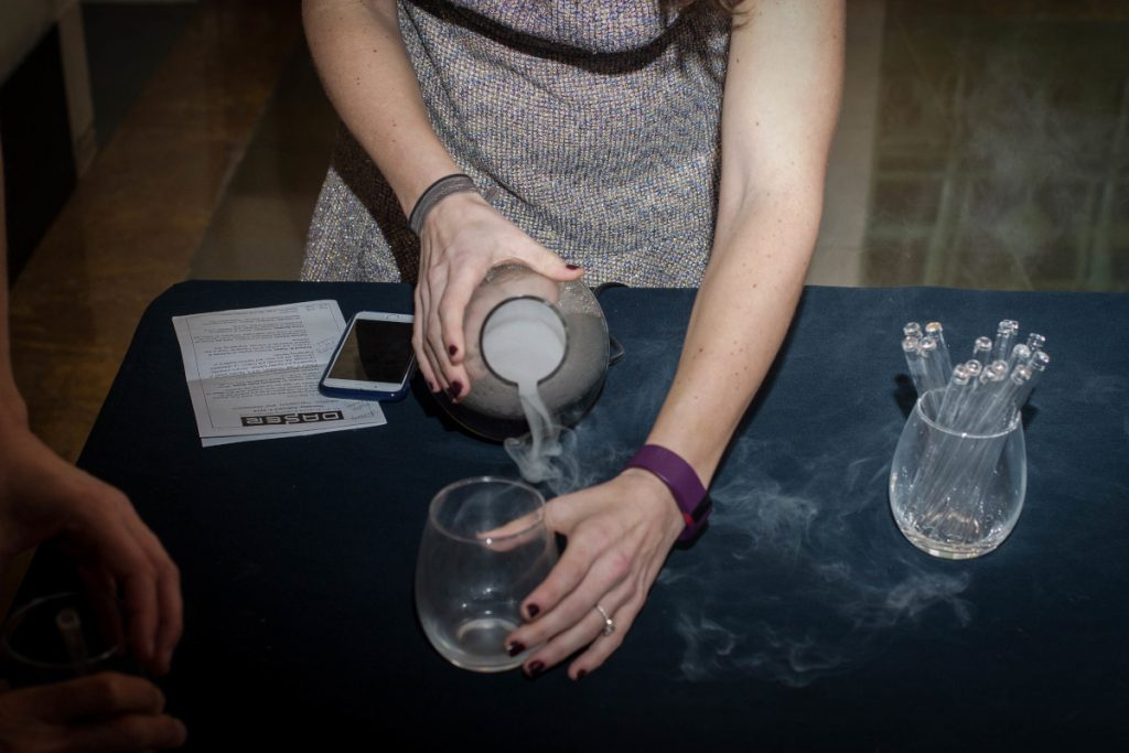 Person pouring a cloudy liquid from an Erlenmeyer flask into a stemless wine glass
