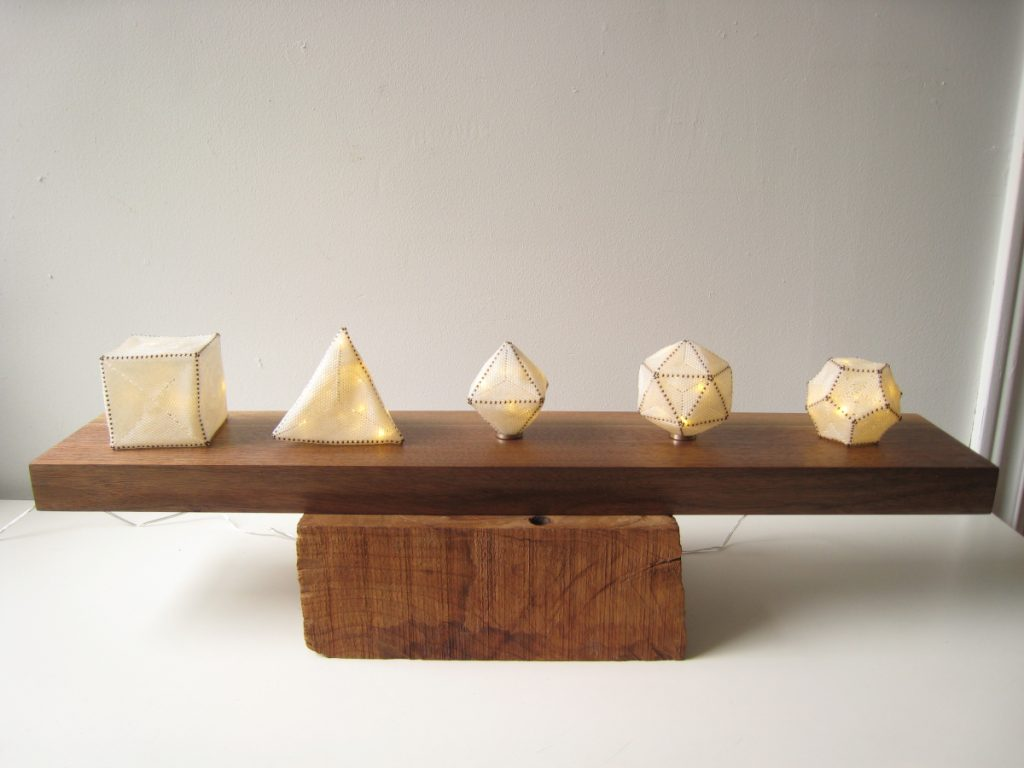 Five cream-colored lamps of different geometric shapes (cube, pyramid, etc.).
