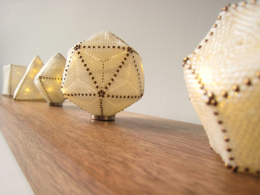 Five cream-colored lamps of different geometric shapes (cube, pyramid, etc.). Close up image.