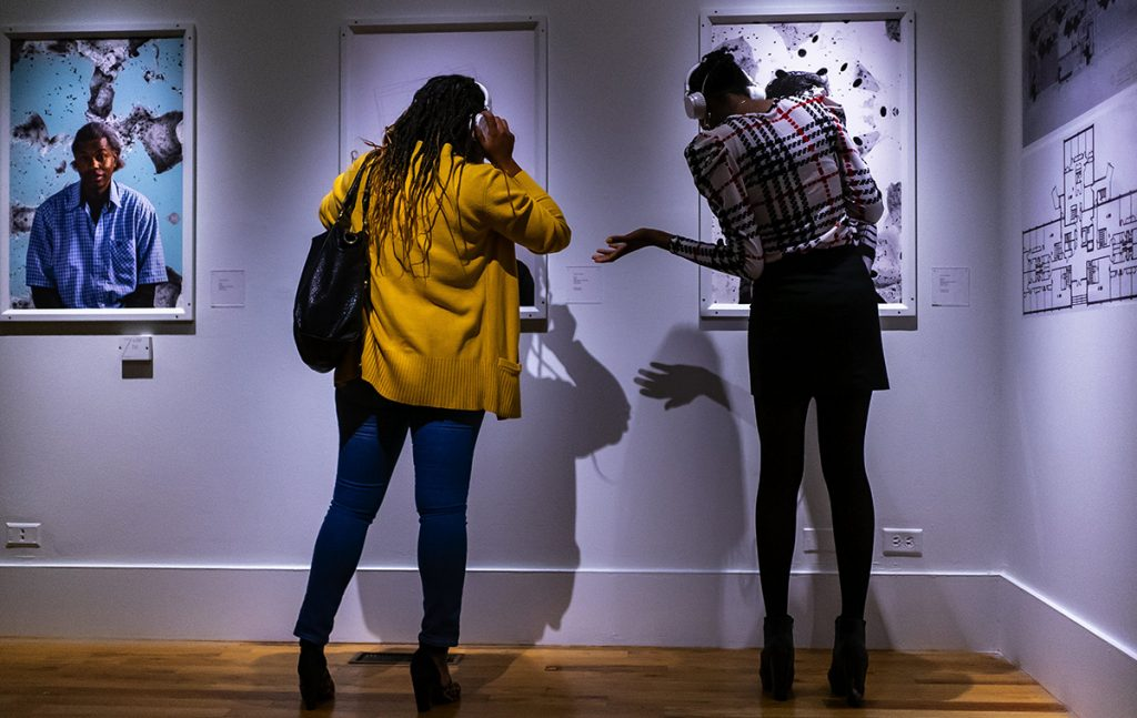 Two women looking at portraits in a gallery and wearing headphones, listening to audio about the exhibition.