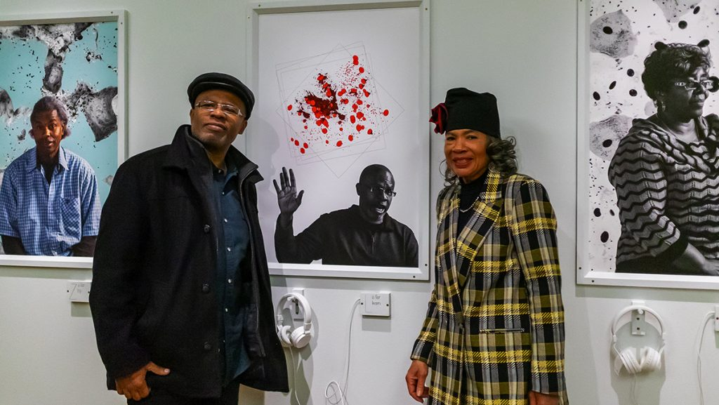 A man and a woman standing in front of the man's portrait at an exhibition.