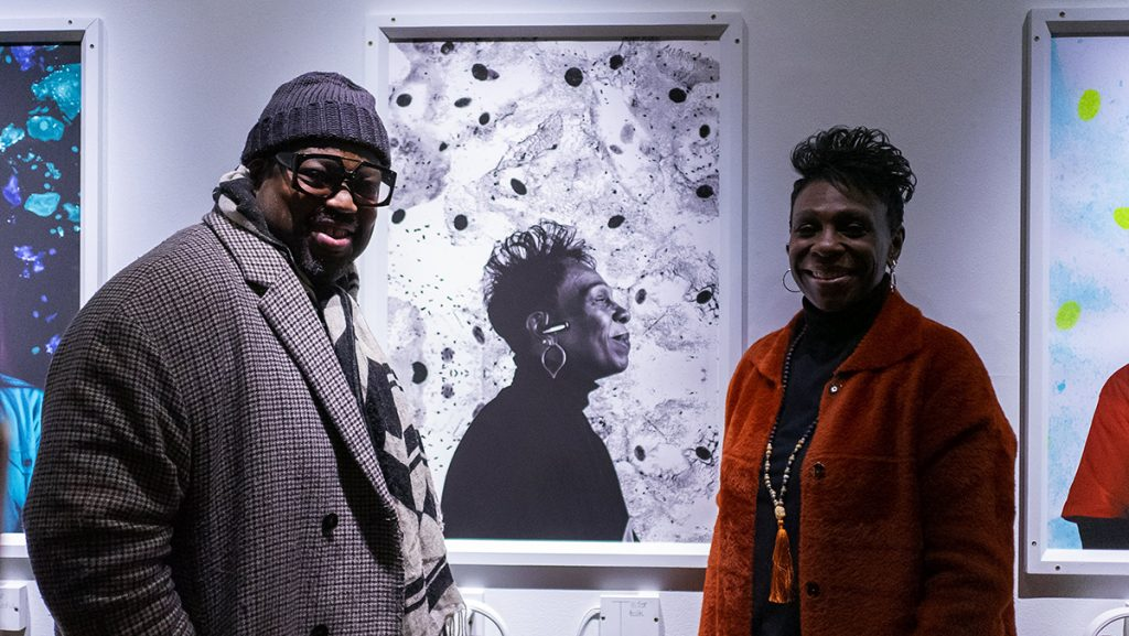 A man and a woman standing in front of the woman's portrait at an exhibition.