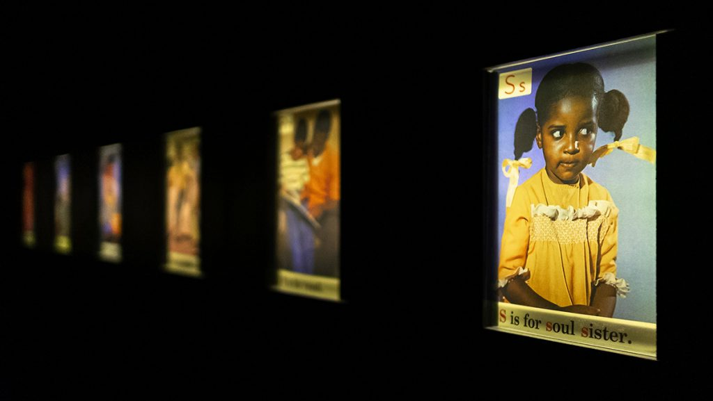 Images of the Black ABC cards on a black background. The closest card has a little girl in a yellow dress.