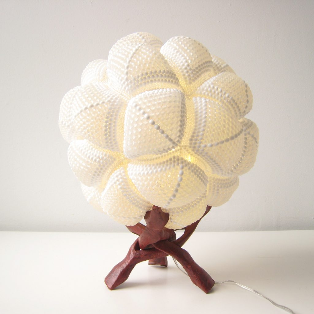 White spherical lamp made of joined beaded triangles.