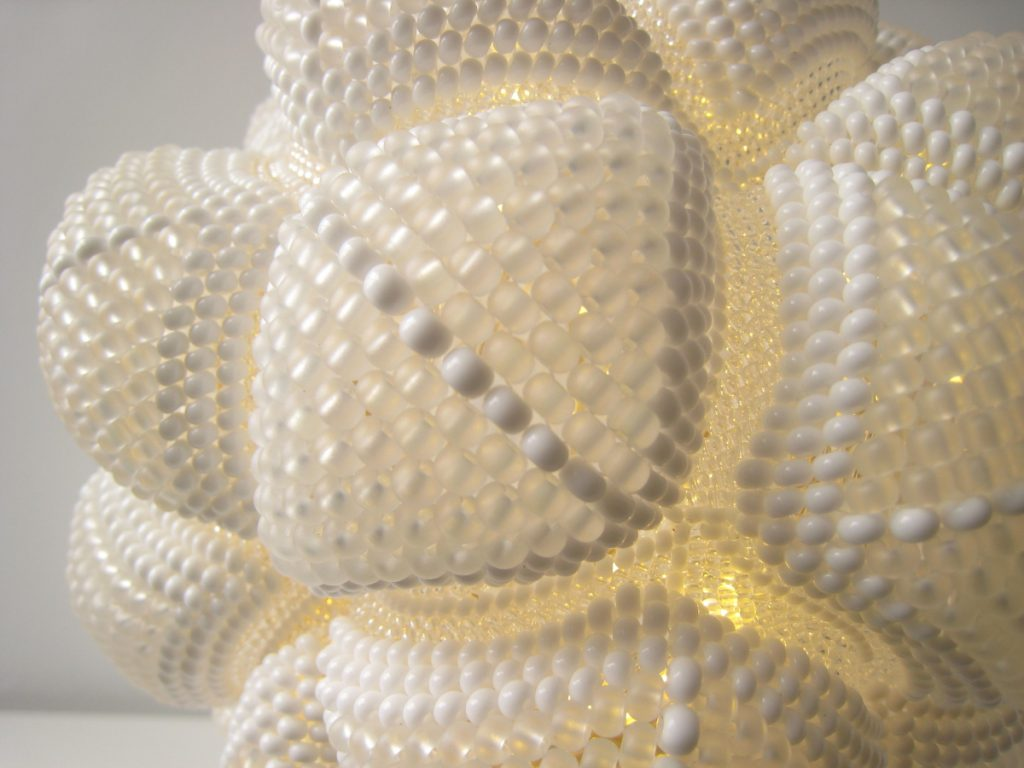 White spherical lamp made of joined beaded triangles. Close up image.