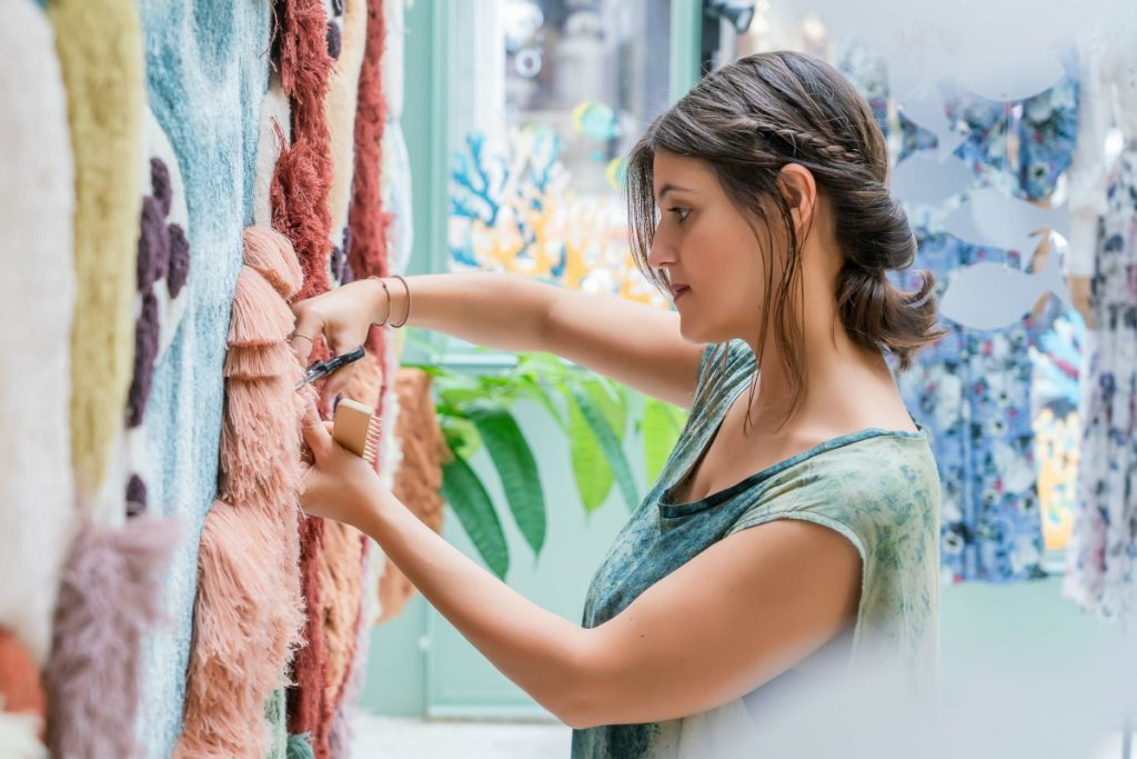 Vanessa trimming yarn on a hanging tapestry.