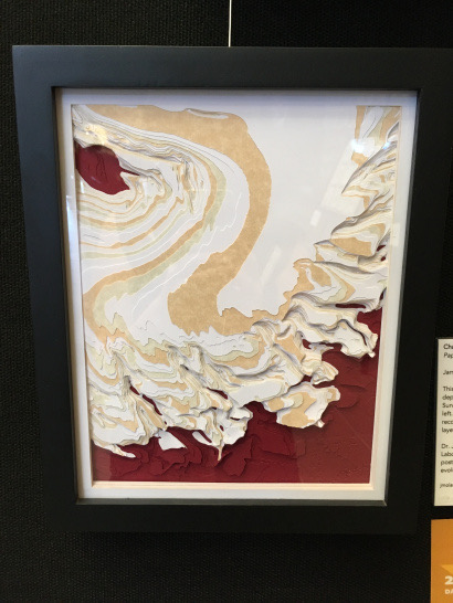 Paper sculture depicting the Martian canyon Chasma Boreale. White, orange, and red paper was used in the piece.