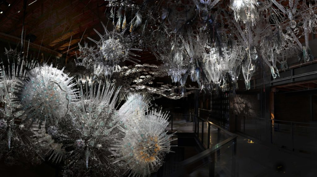 View of the icy sculpture with its feathered hanging pieces and illuminated starbursts.