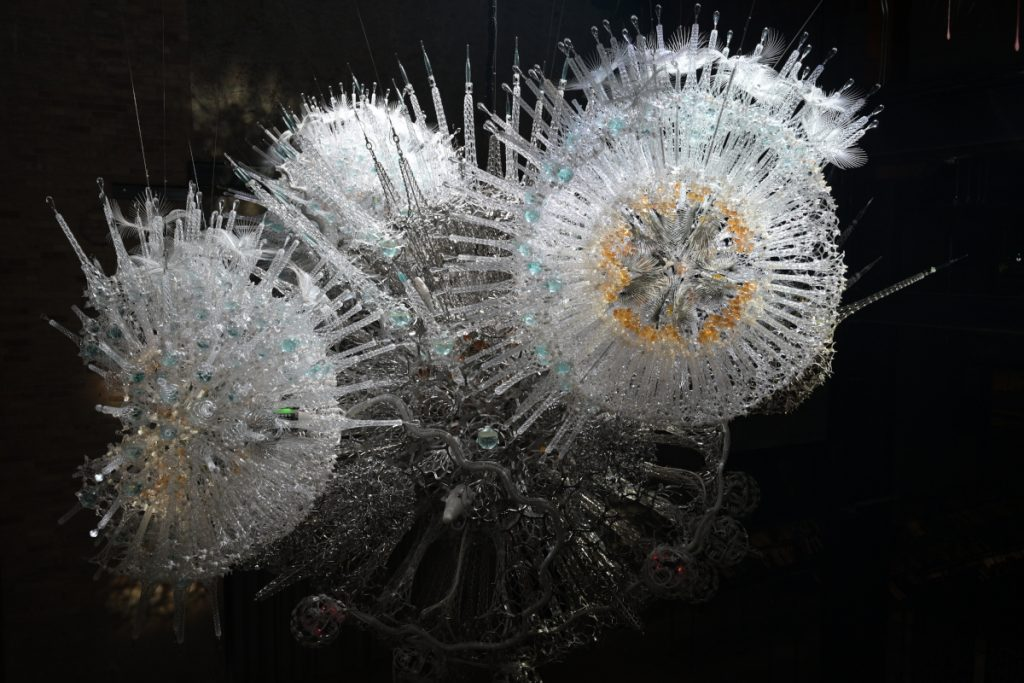 Starbursts comprised of clear plastic rods that looks like icicles and mesh made of metal