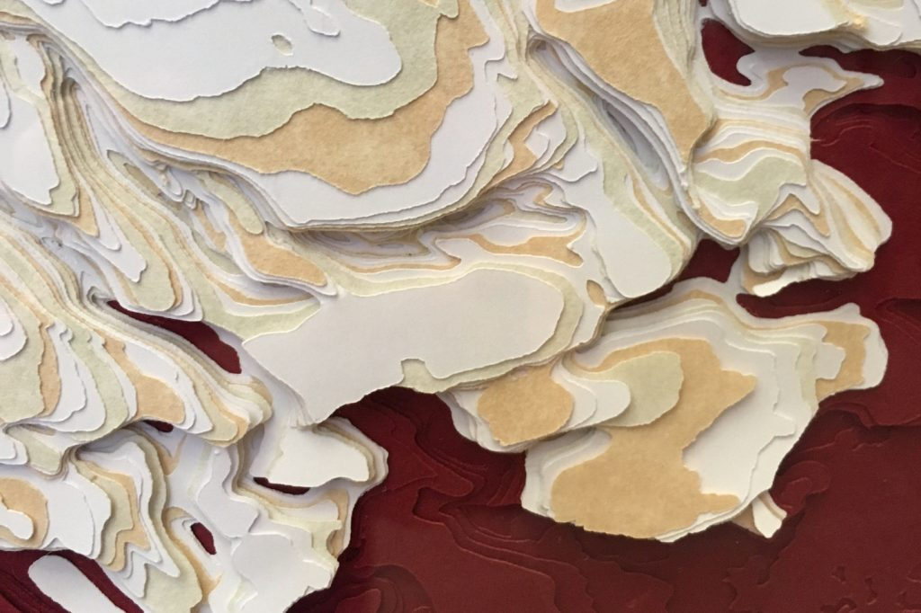 Close up of a paper sculture depicting the Martian canyon Chasma Boreale. White, orange, and red paper was used in the piece.
