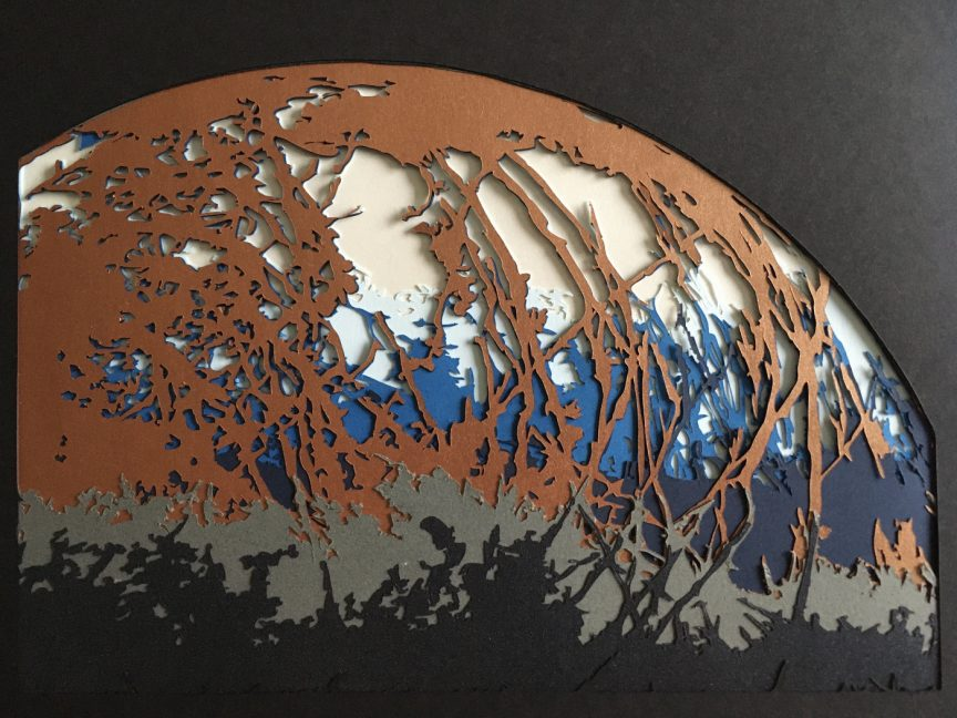 Round cutout of Jupiter's moon Europa on black paper. Europa contains branching streaks of orange-brown, blue, black, and gray.