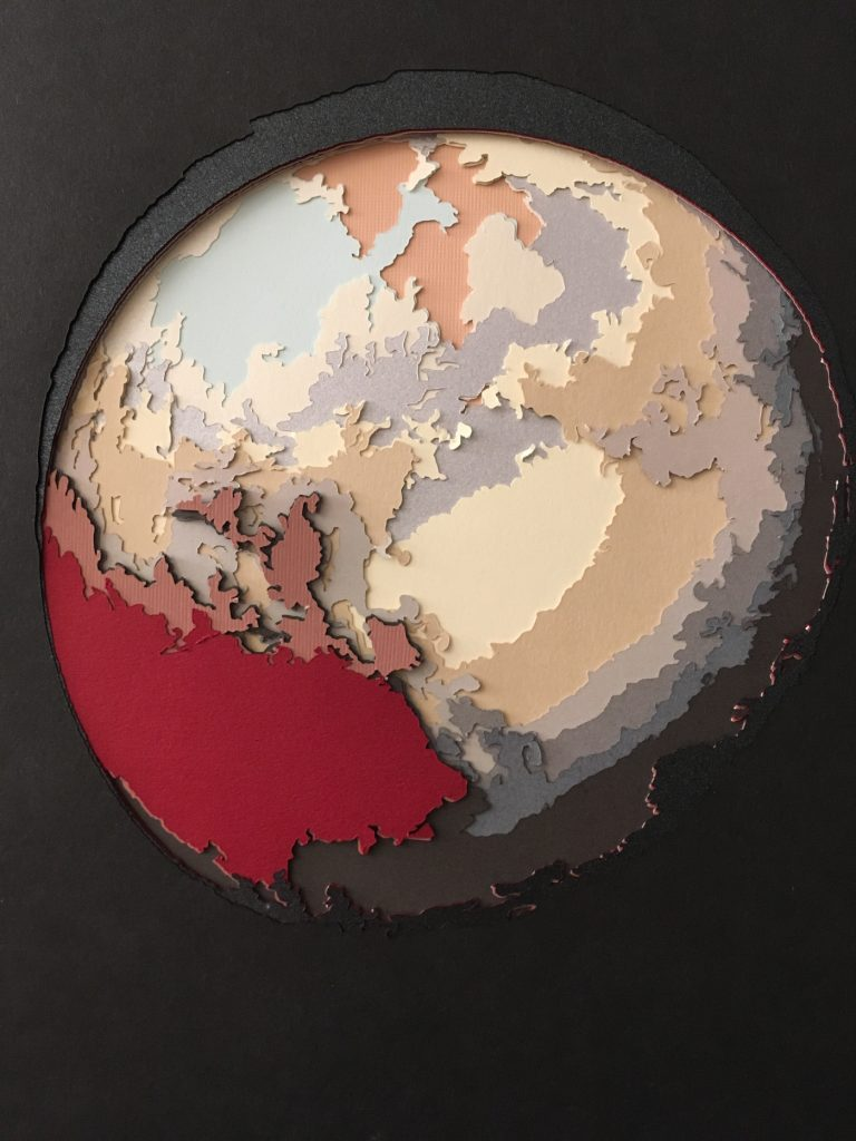 Paper sculpture by Jamie Molaro that  depict the round dwarf planet Pluto. Red, mustard yellow, and gray paper was used in the piece.