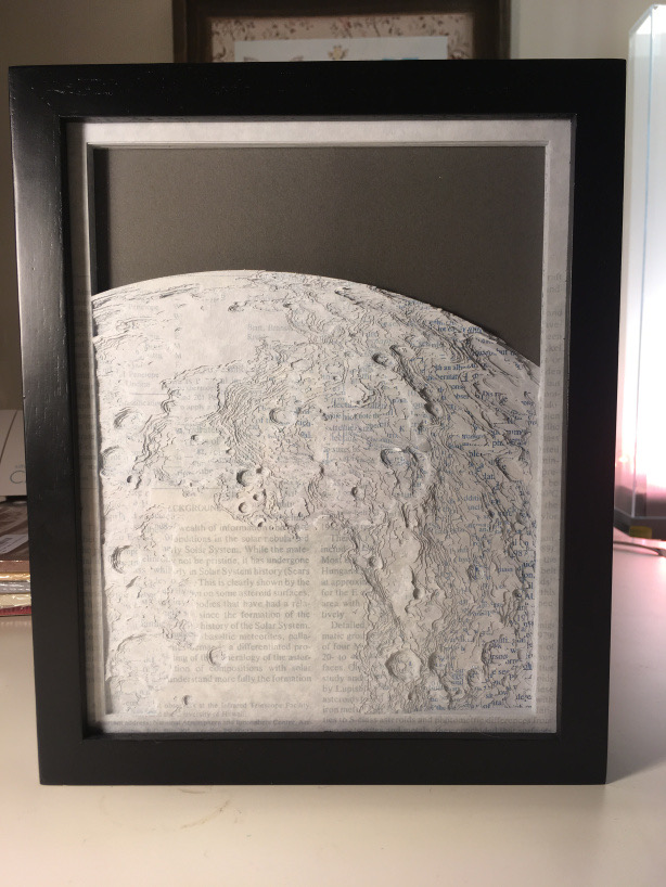 Paper sculpture that depicts the dwarf planet Ceres. Uses layers of scientific papers as the medium onto top of a black backdrop.
