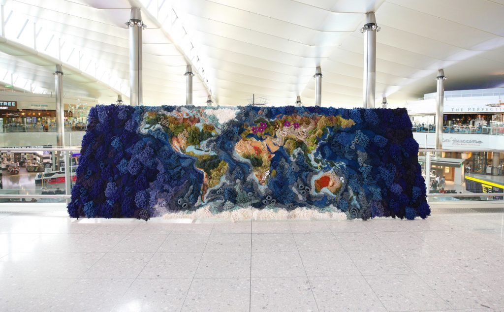 The Botanical tapestry, which shows a colorful world map and displays threatened flowers and corals. The tapestry is sitting in a terminal in Heathrow Airport.