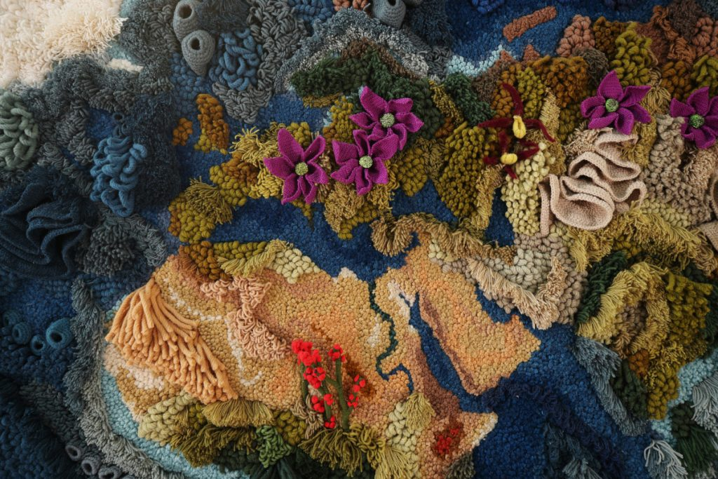 Close-up of the Botanical tapestry showing the different flowers and corals incorporated into the work.