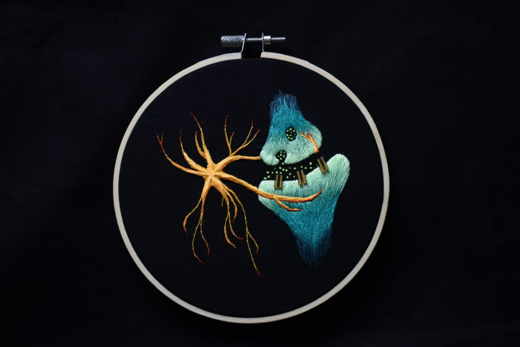 """A custom order creating a neuronal synapse with a supporting astrocyte (""""star-shaped"""" cell). Beads detail the receptors, which bind neurotransmitter shown by tiny knots within the synaptic cleft."""