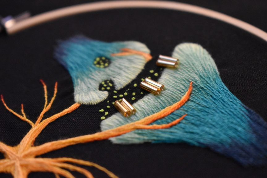 Embroidery showing a synapse with green dots being transferred from one neuron to another over a small gap.