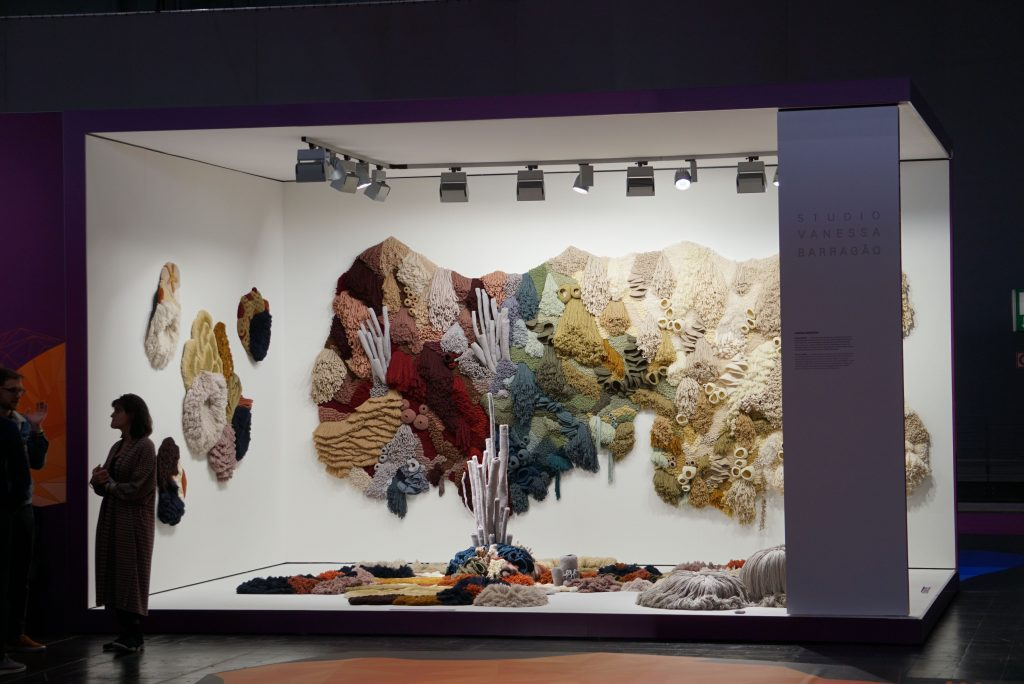 Multiple tapestries, some on the ground, some on the wall, and a large one hanging in the back within a large display. There are many colorful corals, but they become white toward the right side of the display.