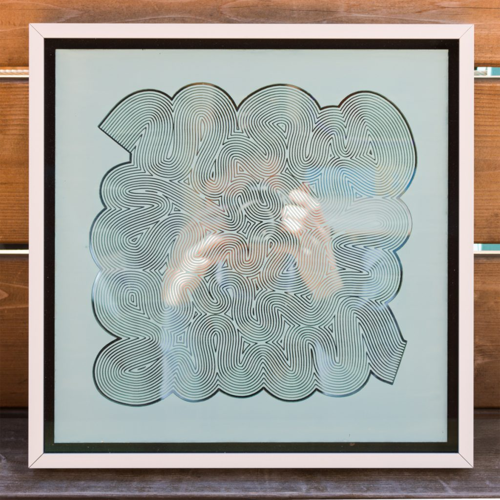 Framed print of silver lines forming a squiggling maze-like pattern. Tyler's is reflected he takes a picture of the print.