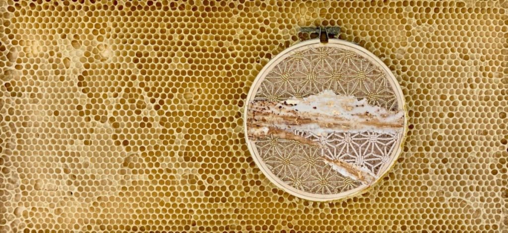 Circular embroidery hoop with cream and gold starburst pattern on tissue paper. The hoop is embedded in honeycomb.
