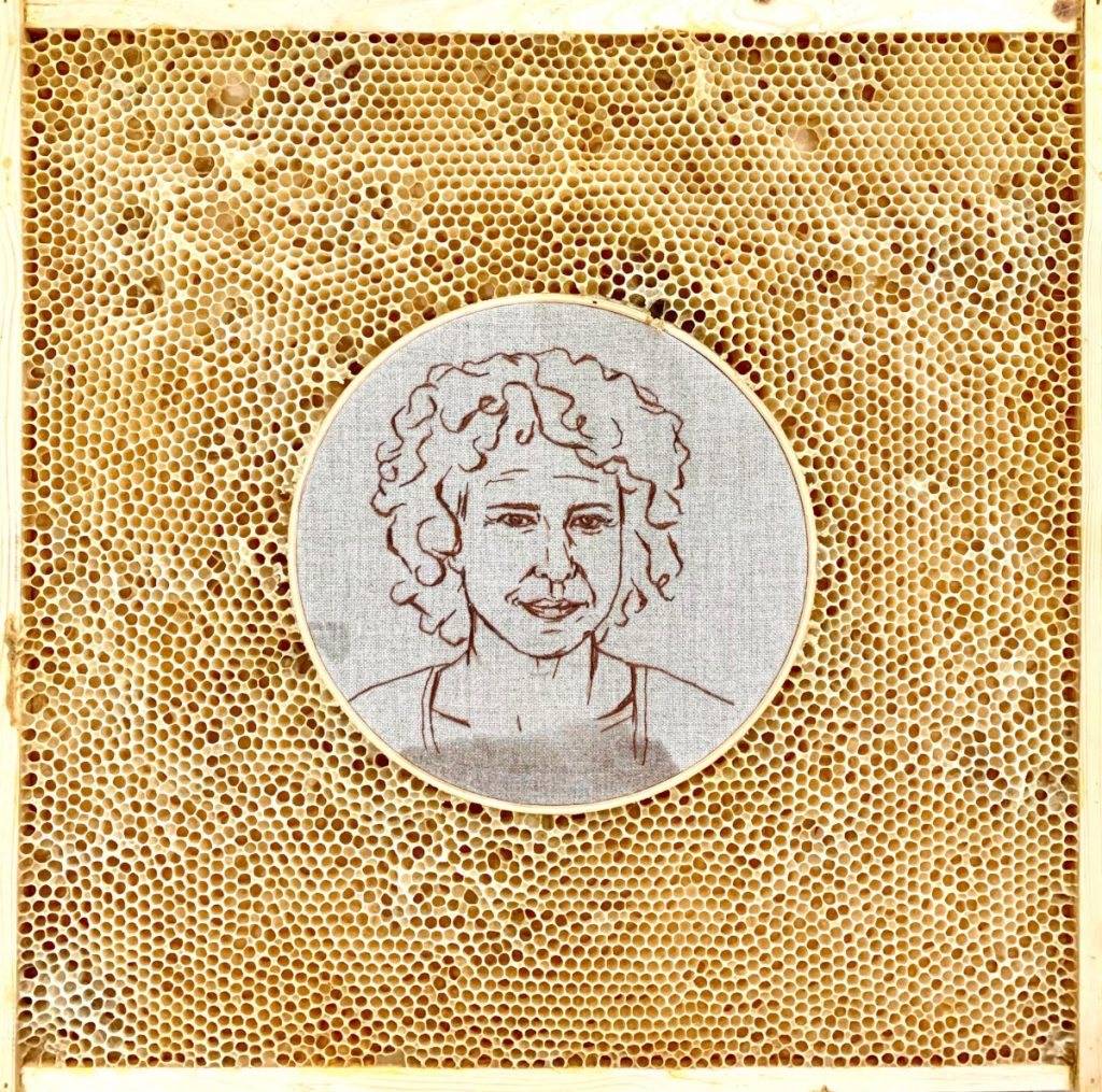 Self portrait of Ava Roth embroidered on linen in a circular embroidery hoop. The hoop is embedded in honeycomb.