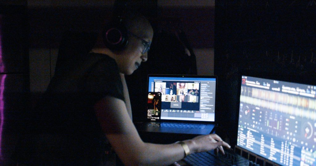 Simón(e) sitting in front of two computer monitors while dj-ing