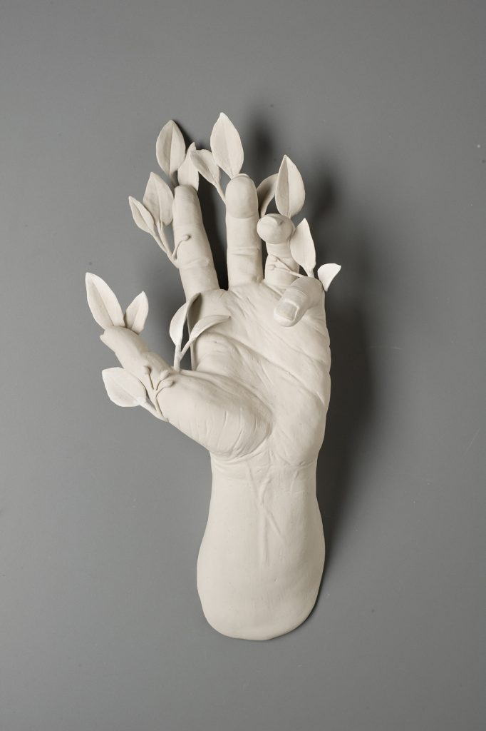 Hand with small leaves surrounding the fingertips