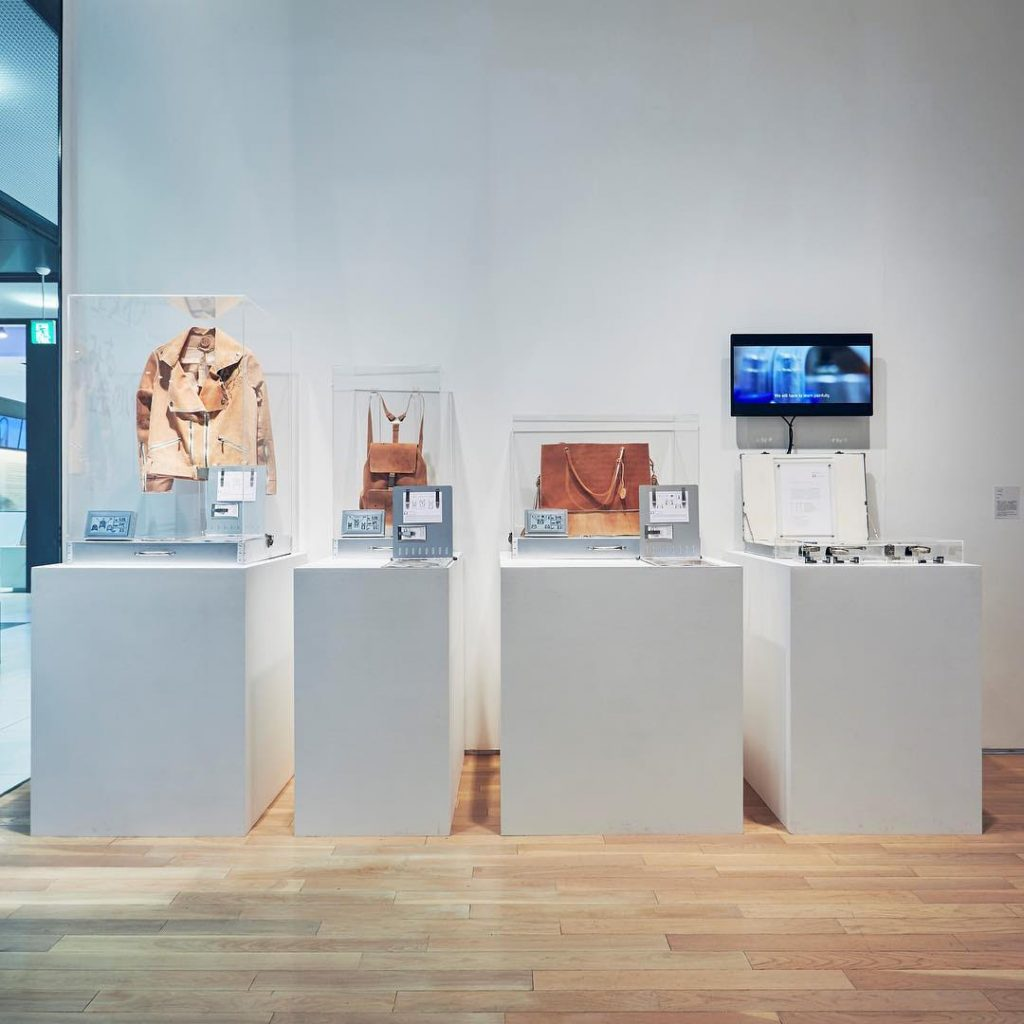 A gallery display of Pure Human 1 with a leather jacket, two bags, and a briefcase containing a patent placed on white podiums.