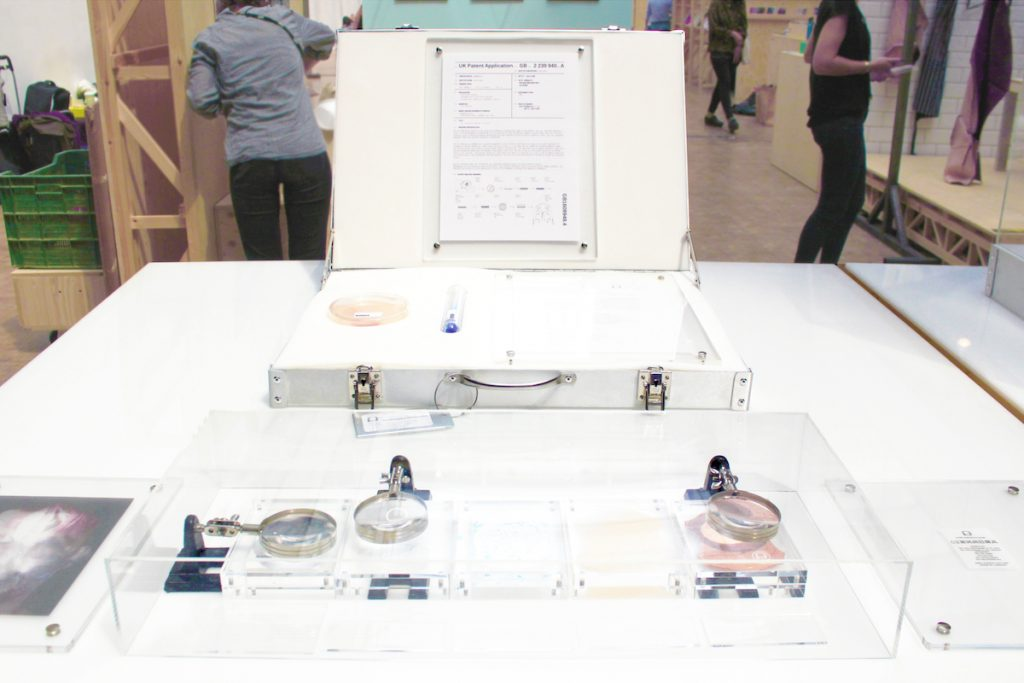 A gallery display of Pure Human 2 with a briefcase containing reagents and a patent on a table. The table also contains a glass case with magnifying glasses hovering over pieces of leather.