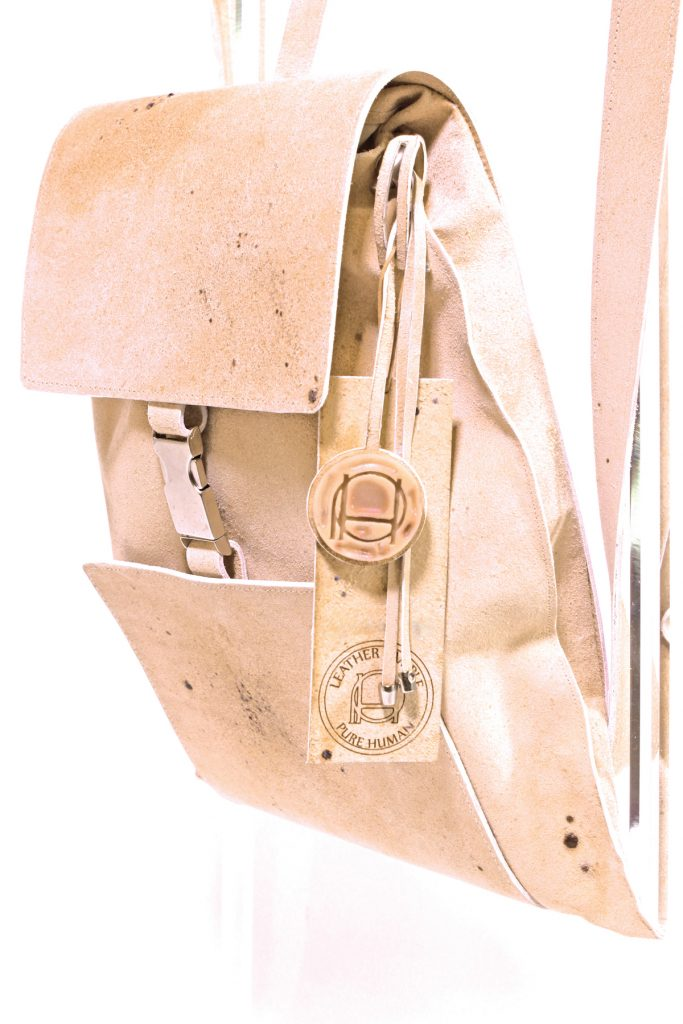 A pale peach-colored leather bag with occasional small brown spots.