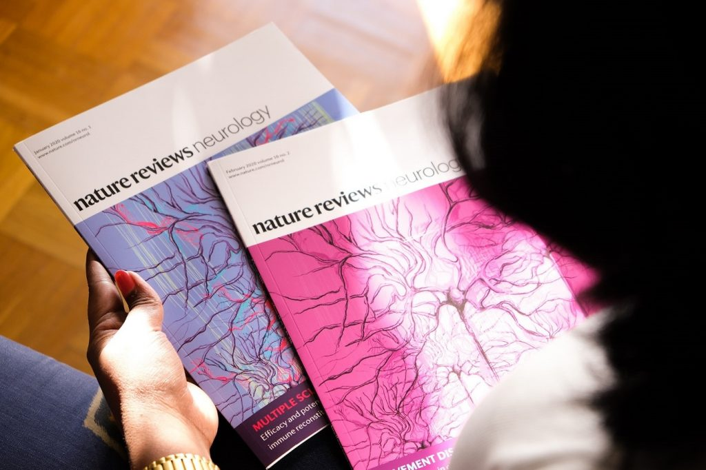The Guardians – Featured on Nature Reviews Neurology (2020) by Dr Radhika.  Dr Radhika holding the nature journal with her cover image of neurons.