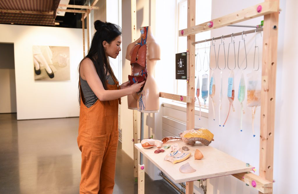 A gallery display of The Self-Donor Workshop with a women replacing an organ from a model of a human torso. Artificial organs and colorful IV bags are on a table nearby.