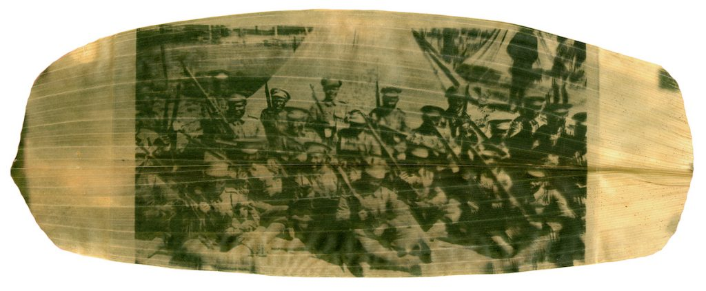 A green and yellow image of soldiers sitting in a group printed on a large, long leaf.