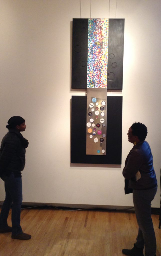 Two people looking at an artwork. Top of the work has colorful paint dots over top of wire shaped into a person's figure. The bottom is made of different sizes of Petri dishes with words on the bottom.