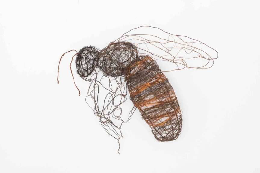 Bee made of lighter and darker colored copper wire