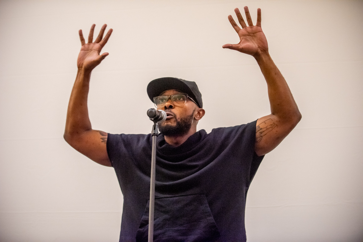 A person with a beard and flat brimmed baseball hat speaks into a microphone. He raises his hands above his head.
