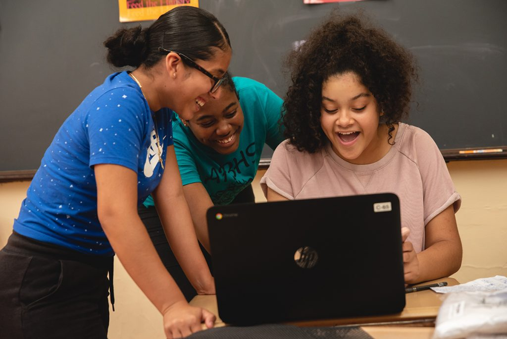 Three girls smiling while working on a laptop