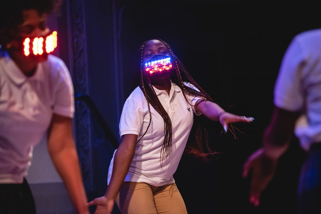 Girls dancing onstage with light-up face masks