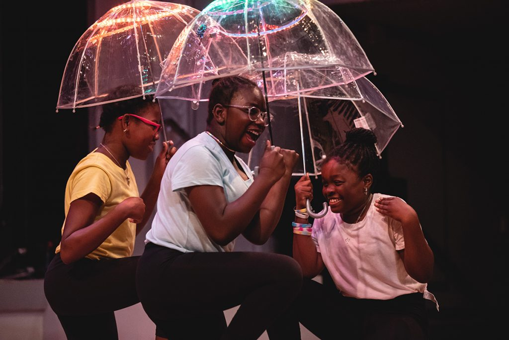 Three girls dancing while holding clear umbrellas with lighting at the top