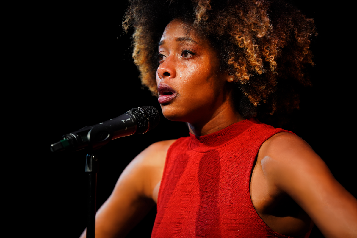 A person speaks into a microphone. The background is dark. There is a tear on her face.