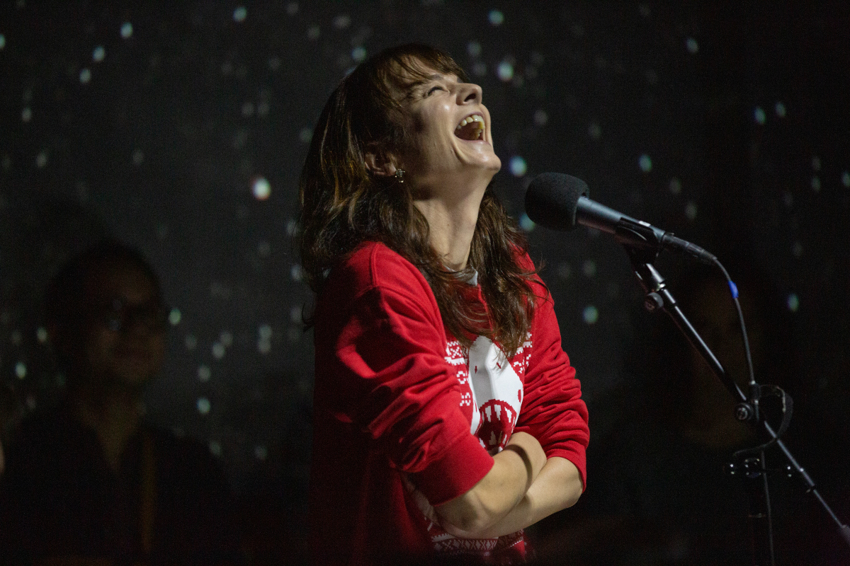 A person laughs in front of a microphone. The background is lit like stars.