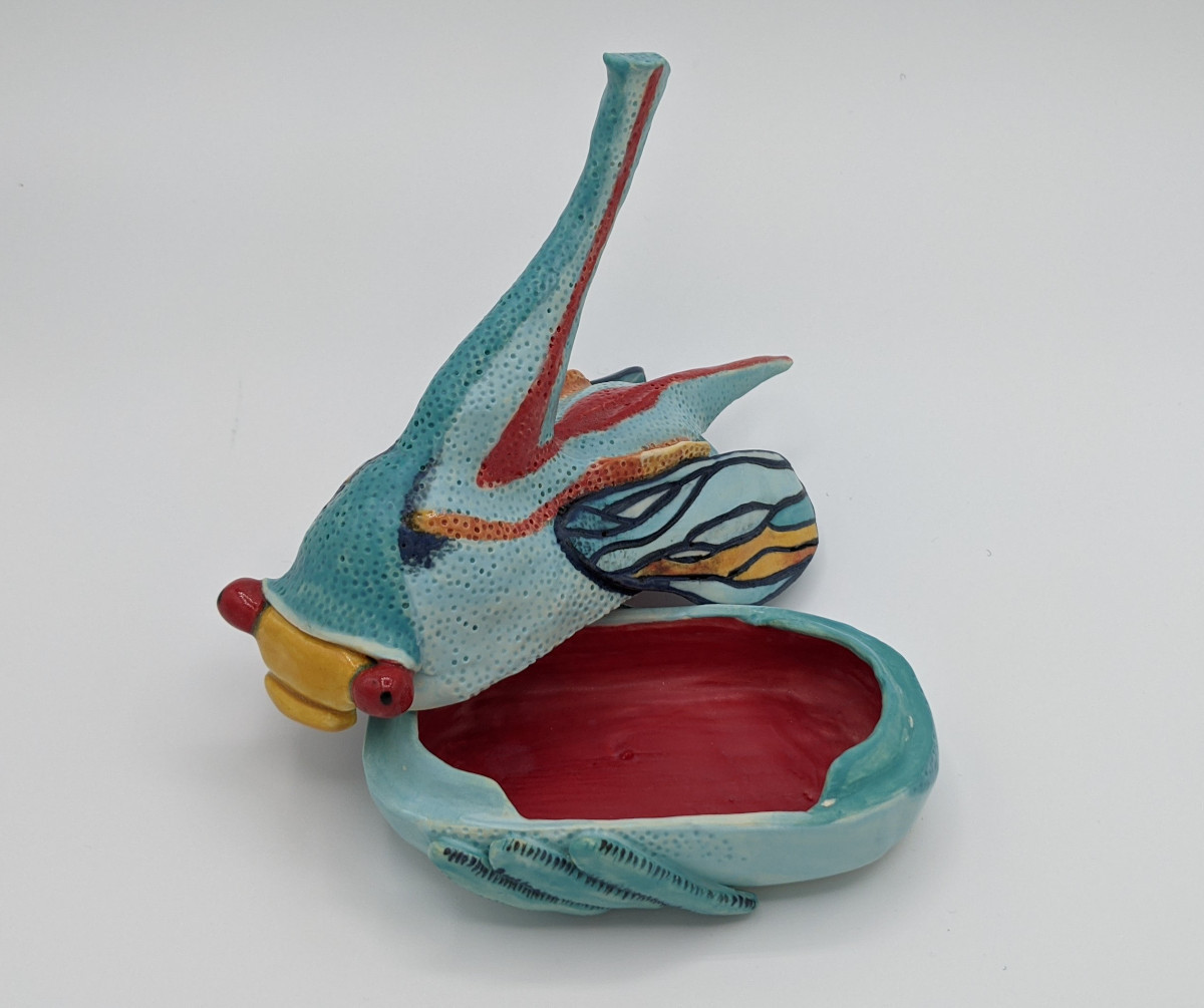 Pottery of light blue insect with long horn-like protrusion from head, small wings, and large red eyes. The insect opens to function as a box.