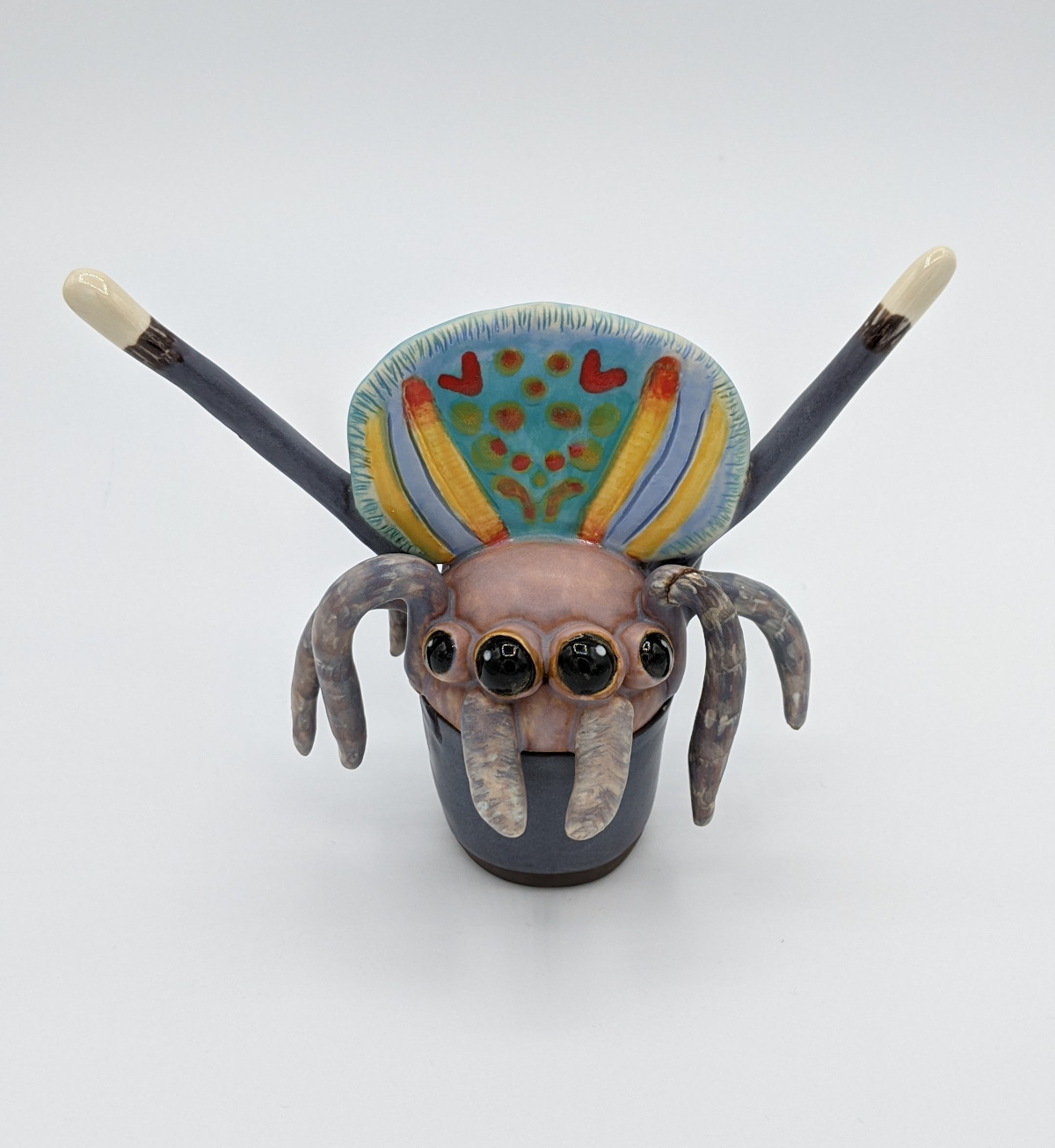 Pottery of a spider with brown head and a colourful body