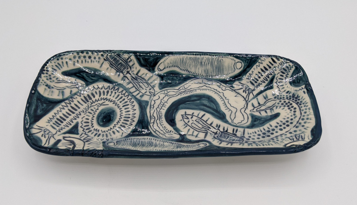 Long rectangular plate patterned with large worms of varying appearance. The worms are outlines in dark blue with white space around them, then surrounded by more dark blue.