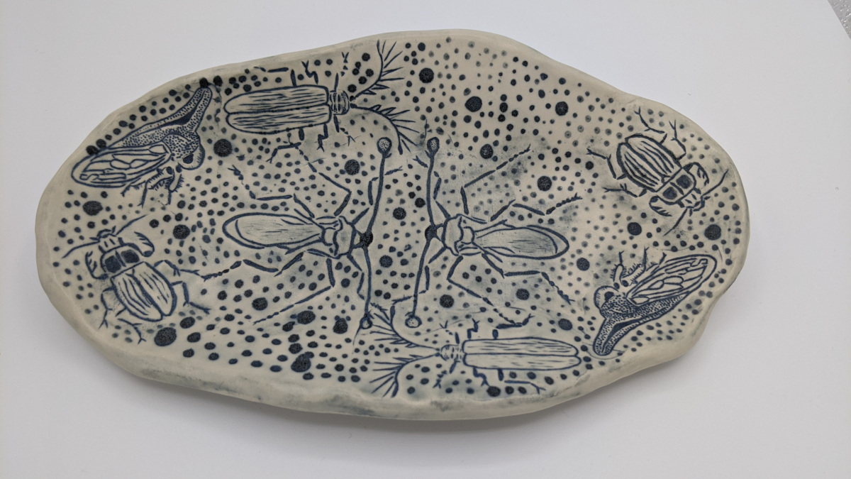 A slightly wavy rectangular plate patterned with various insects surrounded by dots. The insects and the dots are dark blue.