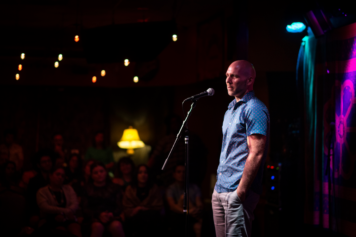 A person stands in front of a microphone. In the background, an audience watches.